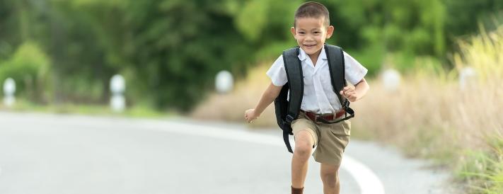 Junge mit Schulrucksack auf dem Weg zur Schule