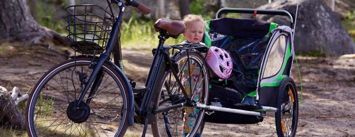 Kind mit Helm vor einem Fahrradanhänger