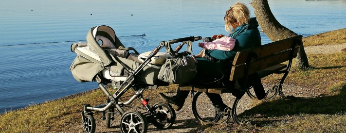 Mutter mit Kinderwagen in der Natur