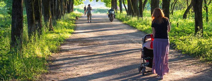Mutter mit Kinderwagen in der Natur