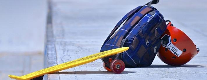 Schulranzen und Skateboard auf dem Gehweg