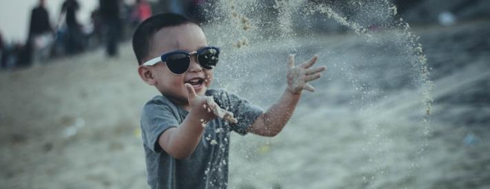 Junge mit Sonnenbrille spielt mit Sand