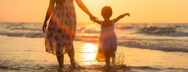 Strandspaziergang mit Kind bei Sonnenuntergang