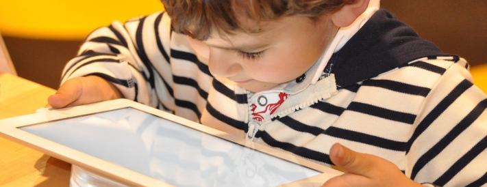 Kind blickt fasziniert auf ein Tablet